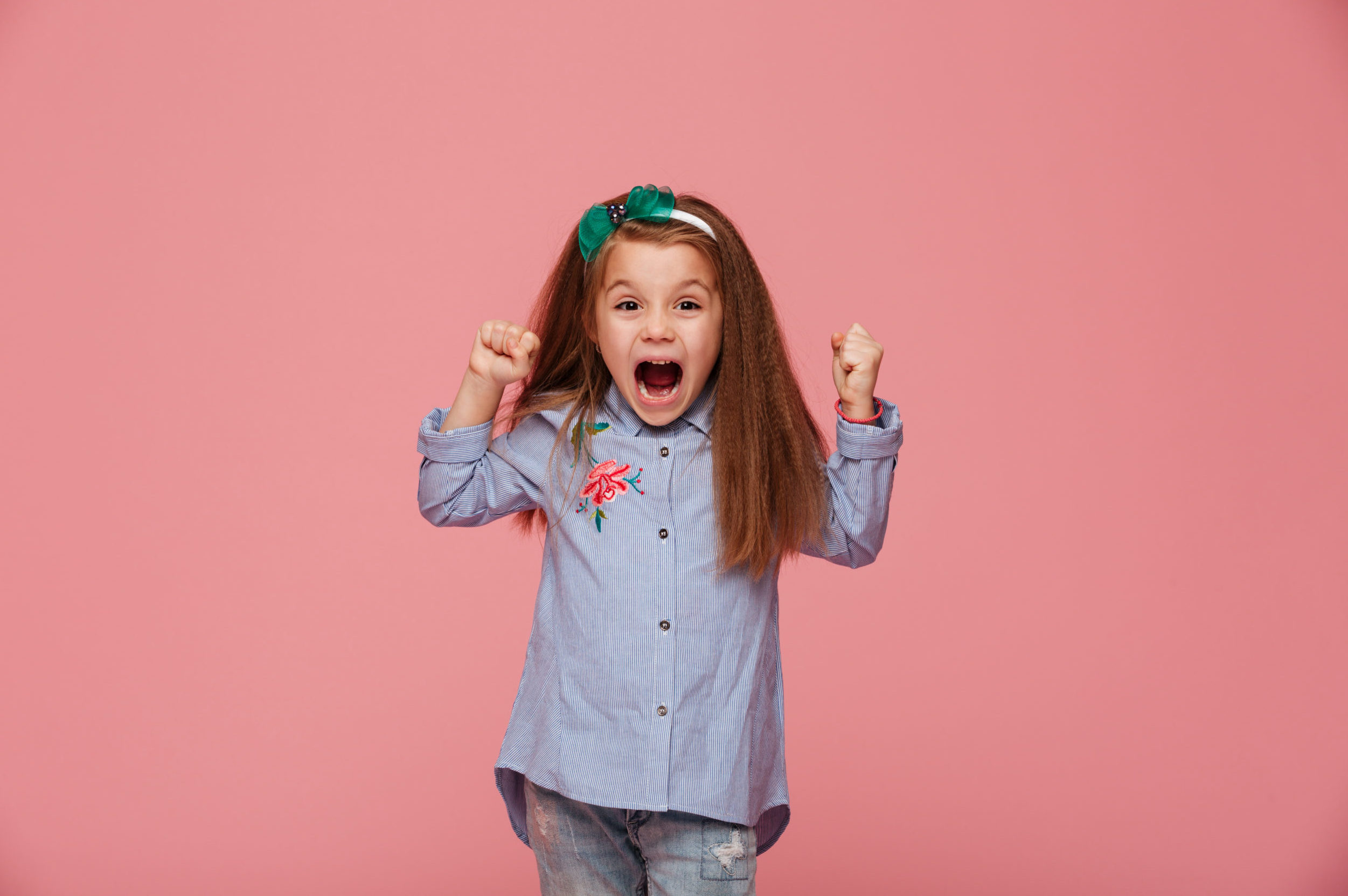 Beautiful female kid in hair hoop and fashion clothes clenching fists, shouting with happiness and admiration against pink background
